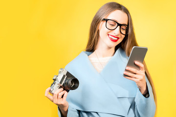 Stylish woman photographer with retro camera and smart phone on the yellow wall background