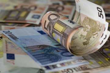 Half rolled fifty euro banknote on  euro banknotes background. Close up shot, Selective focus.