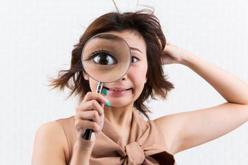虫めがねを覗く女性