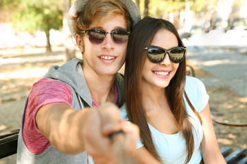Happy couple taking selfie on street