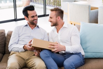 Smiling man offering gift to his boyfriend