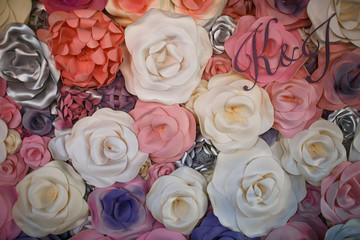 White, pink and silver cloth flowers and initials over them