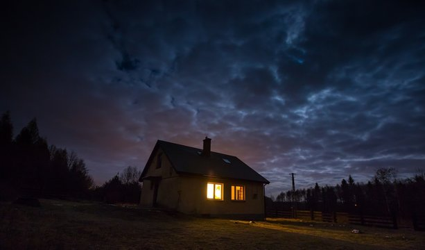 Landscape with house at night under cloudy sky