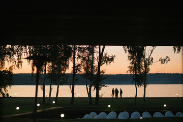 Look from inside at people standing on the lake's shore in the e