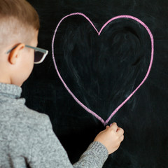 Little boy draws with chalk heart.