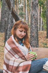 Beautiful red haired young woman with blanket and cup of coffee on a bench at the autumn park. Coloring and processing photo