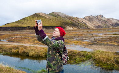 Iceland tourist young woman taking selfie photo with smartphone camera at landmark destination:Landmannalaugar.  Beautiful Icelandic Nature.