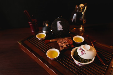 The Chinese tea items. Chinese tea set. Porcelain gaiwan, three cups with tea, pancake of traditional Chinese puer tea, siphon and golden frog on tea desk. Soft selective focus.
