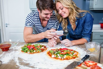 Smiling couple preparing pizza
