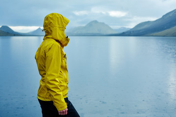 woman on the Lake coast with mountain reflection at the rainy day, Iceland