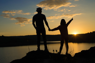 A couple in love holding hands watching beautiful bright sunset under river