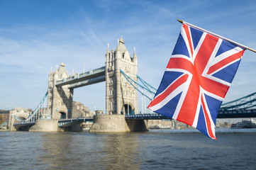 British Union Jack flag flying in front of Tower Bridge in London, England