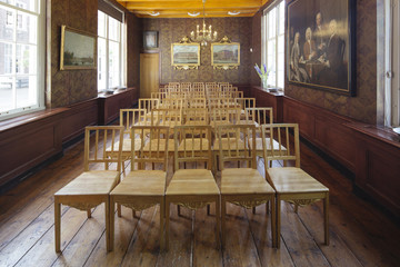 A room in a classical Dutch interior with many chairs used for ceremonies.