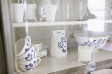 A blue and white crockery set through a glass door of a kitchen cupboard.