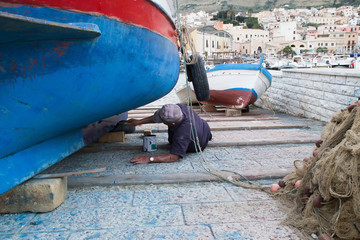 in a small harbour of sicily, a fisherman restayling his boat