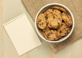 Chocolate chips cookies in bowl with notepad for copyspace