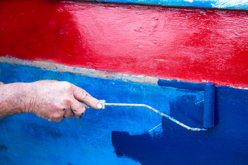 the hand of an old man  painting his boat