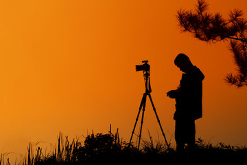 silhouette A man asia with backpack taking a photo on the top of