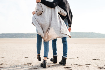 Young couple in casual clothes walking along seashore