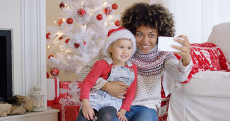 Woman and child posing for camera phone in front of white Christmas tree decorated with red ornaments