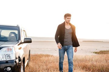 Serious young casual man walking near his car outdoors