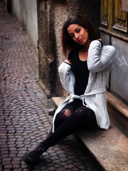 Winter outfit - street portrait of a beautiful young Moroccan girl with brown hair, wearing black sheath dress, grey cardigan sweater, black stockings, grey leather woman boots.