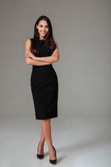 Lovely cute smiling young woman in black dress and shoes ]