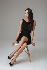 Woman in black dress sitting on chair and looking up