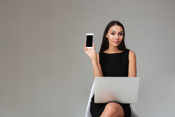 Woman sitting with laptop and showing blank screen mobile phone