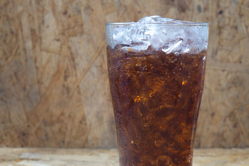 close up soft drink with ice on the grass