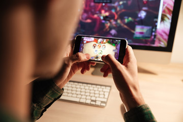Closeup of man playing videogame on smartphone in evening