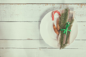 Country style christmas decoration. White empty plate, red apple and Christmas cookies with fir tree, candy, fork and knife tied with a green ribbon on light wooden background.