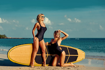 Healthy happy fit surfer girls posing with surfboard on sea beac