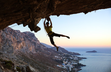 Young man rock climbing in cave at sunset