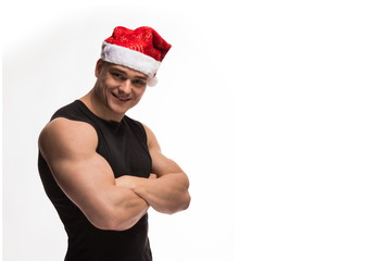 athlete bodybuilder posing with a beard and a cap of Santa Claus on a white background