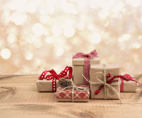 Christmas gift boxes on wooden table over abstract lights background