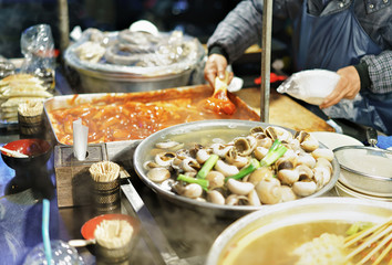 Person selling food at Myeongdong open street market in Seoul