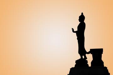 Buddha image in walking posture on orange background with sun