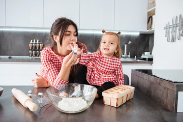 Beauty girl with mom on kitchen