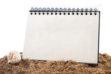 Desktop Loop wire binding book on sand and  isolated white background.