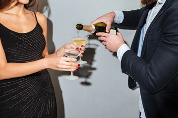 Male pouring champagne into glasses holding by a female