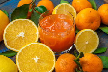 Healthy fresh citrus juice (two glasses), oranges, tangerines, lemons, ice, leaves.  Love for a healthy raw food concept