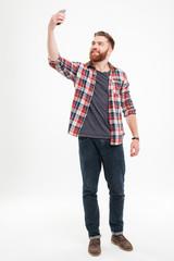 Cheerful bearded man in plaid shirt taking selfie