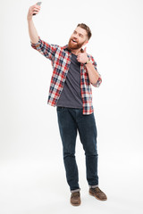Man taking selfie and showing thumbs up gesture