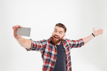 Portrait of a cheerful man taking selfie with raised hand