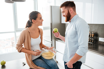 Woman sitting on table in kitchen with man