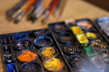 Paint colors and brushes on table
