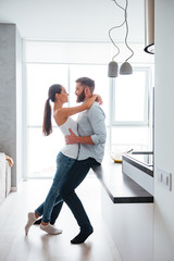 Full length portrait of couple cuddling and kiss