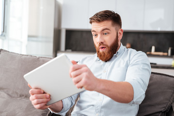Bearded man with tablet on sofa