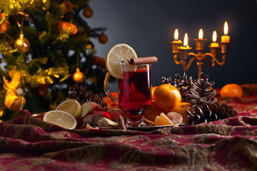 Mulled wine with spices and tangerines before Christmas tree